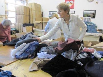 Fleißige Frauenhände prüfen und verpacken die Kleidung schon bei der Annahme